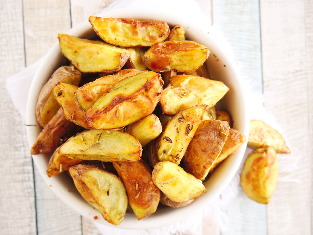 White bowl of roasted red potatoes.