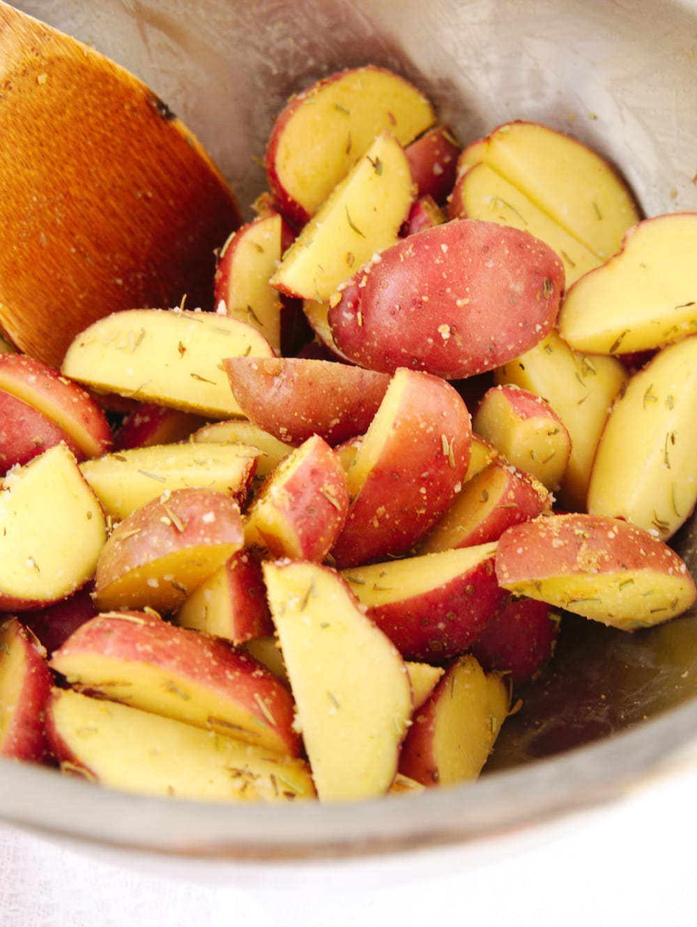 Red potatoes coated with oil and seasonings.