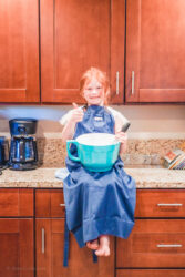 A little girl sitting on a kitchen counter in a large blue apron and smiling.