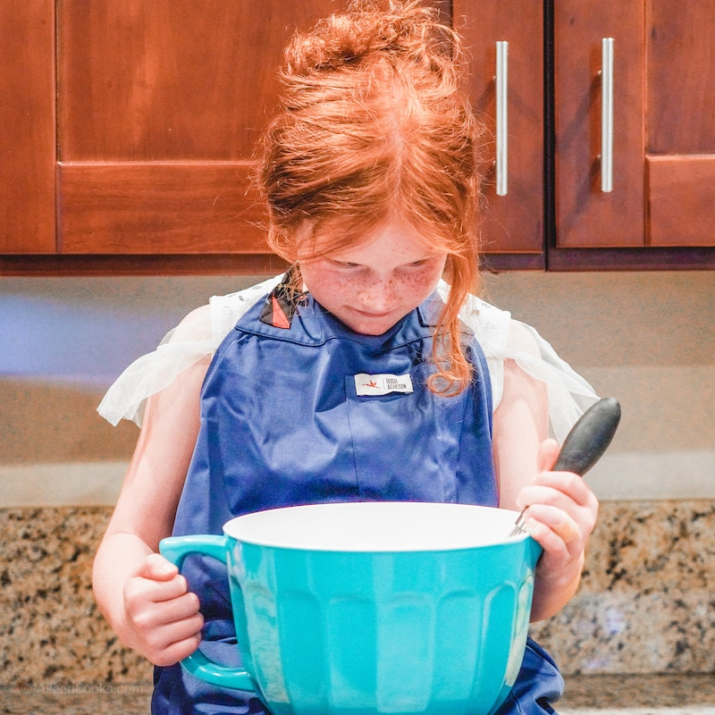 A little girl sitting on a counter in a blue apron and looking down into a blue mixing bowl.
