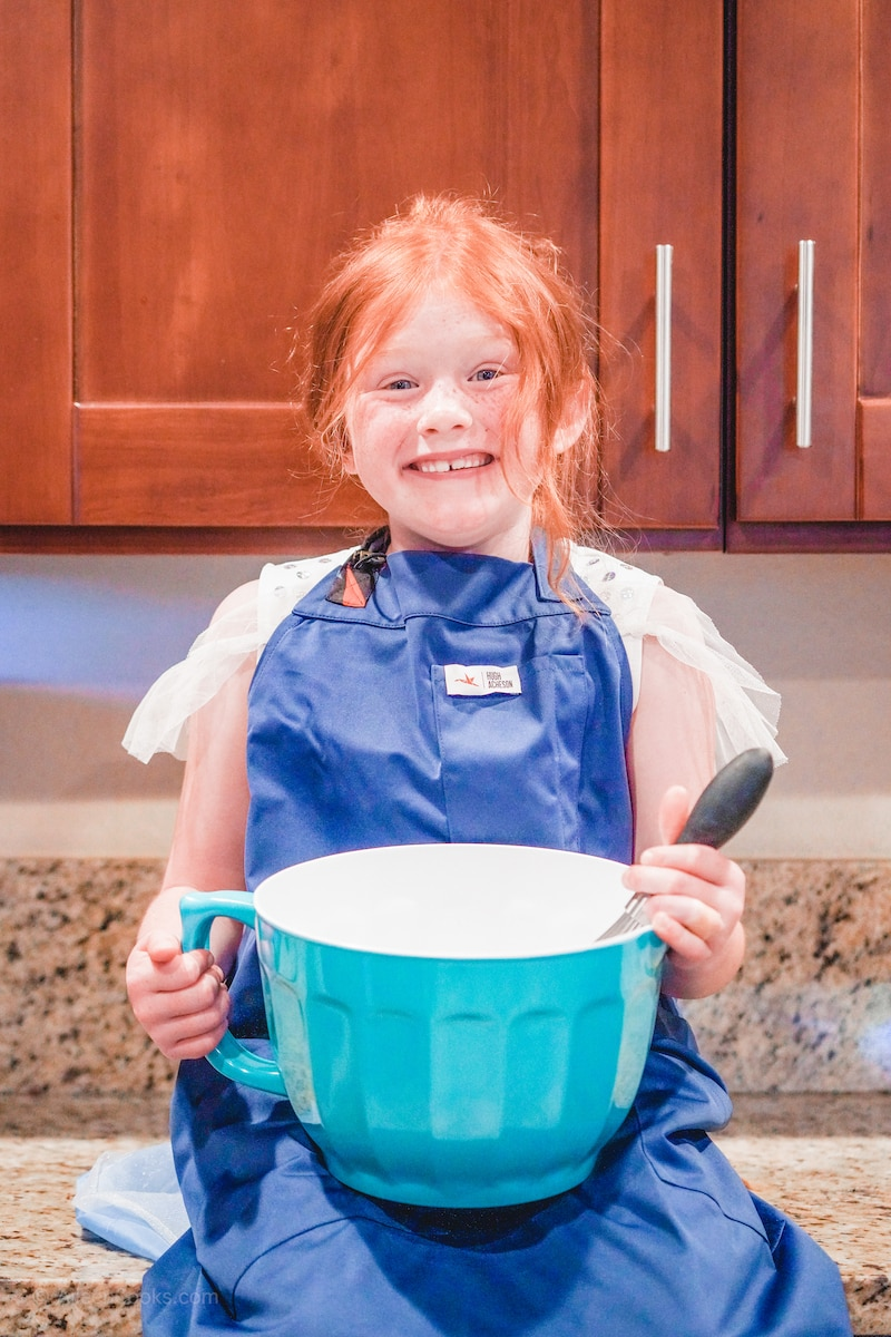 A girl wearing a blue apron and holding a mixing bowl.