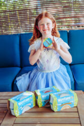 A girl sitting on a blue couch and holding up a Wayfare Pudding Cub.