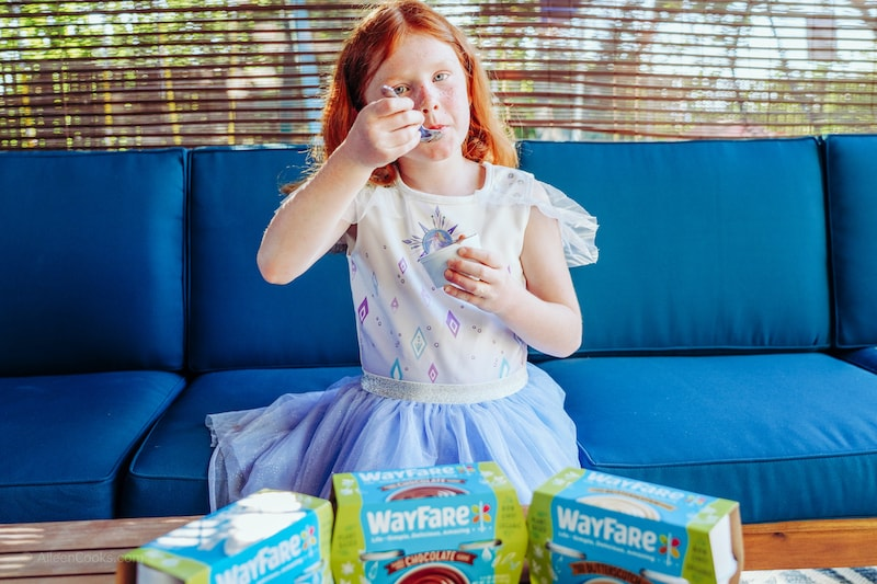 A girl sitting on a blue couch, eating chocolate pudding.
