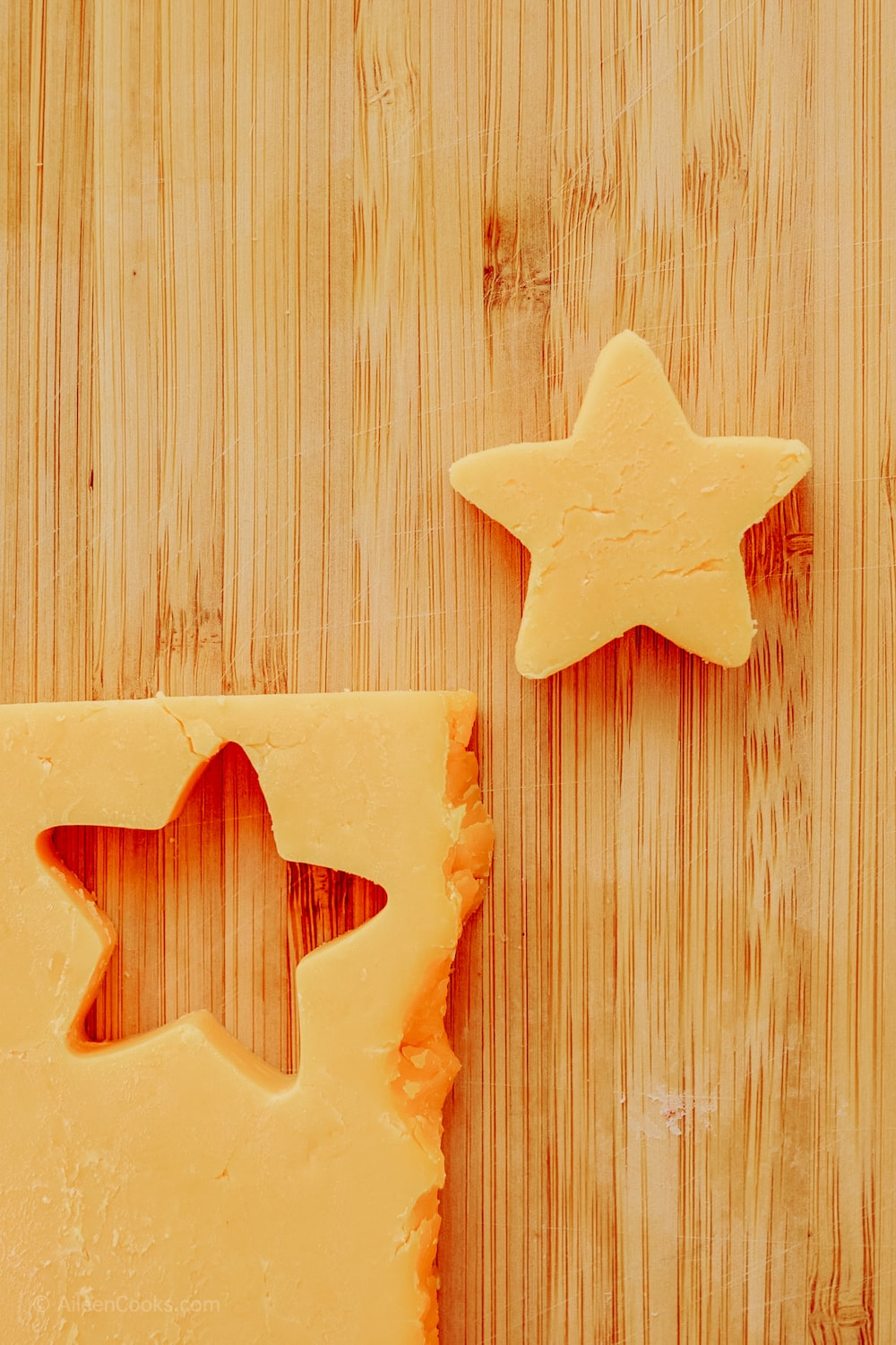 Cheese cut into star shapes on a wooden cutting board.