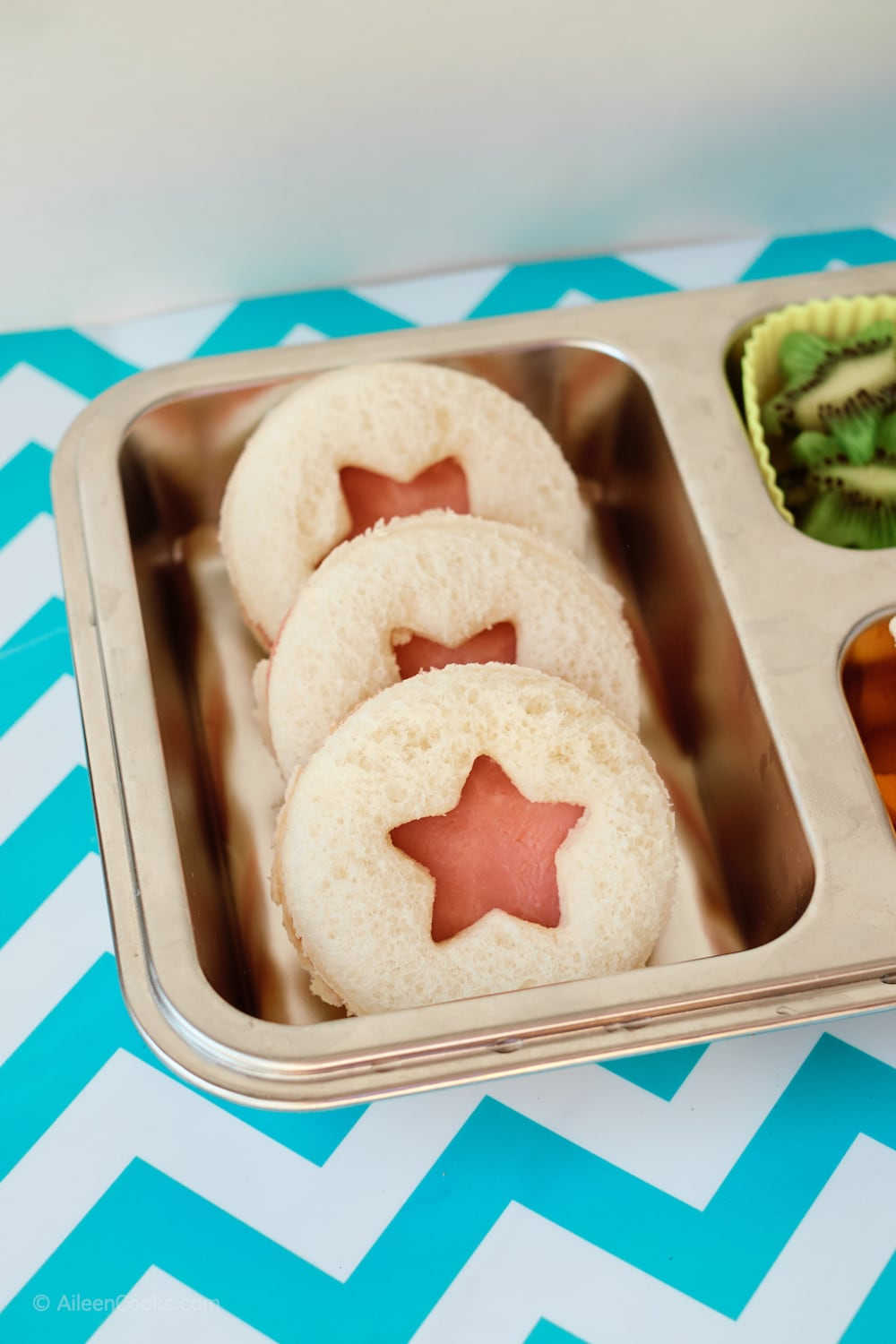 Three ham sandwiches cut into circles with star cut-outs in the center.