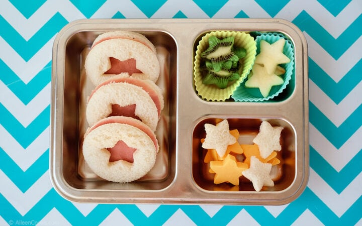 A silver bento box filled with sandwiches, fruit, and cheese; all cut into star shapes.