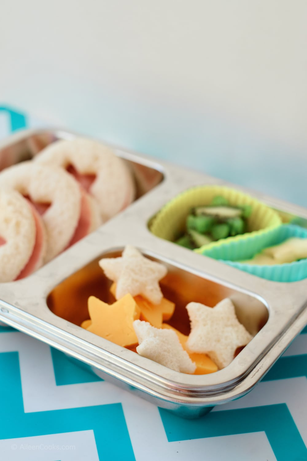 A bento box filled with star shaped cheese, bread, fruit, and ham sandwiches.