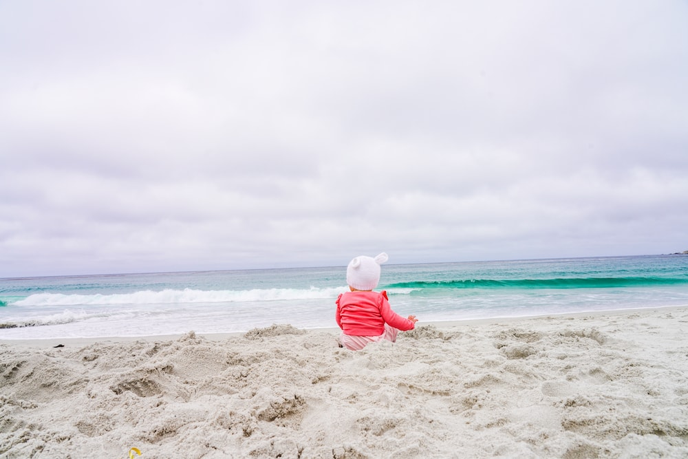 A baby sitting on Carmel Beach, looking at the Pacific Ocean.