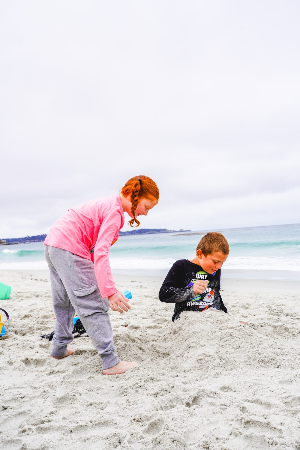 A boy and girl playing in the sand at Carmel Beach