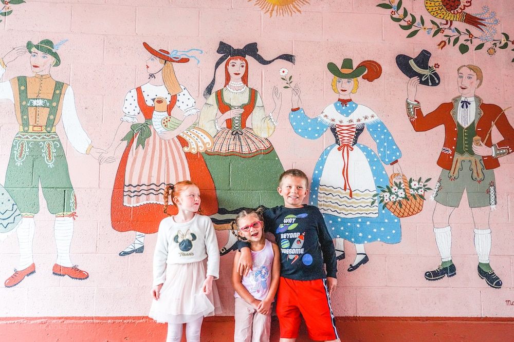 Three kids standing in front of a mural at Hofsas House Hotel.