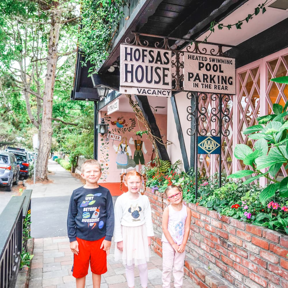 Three kids standing under the Hofas House Sign in Carmel.