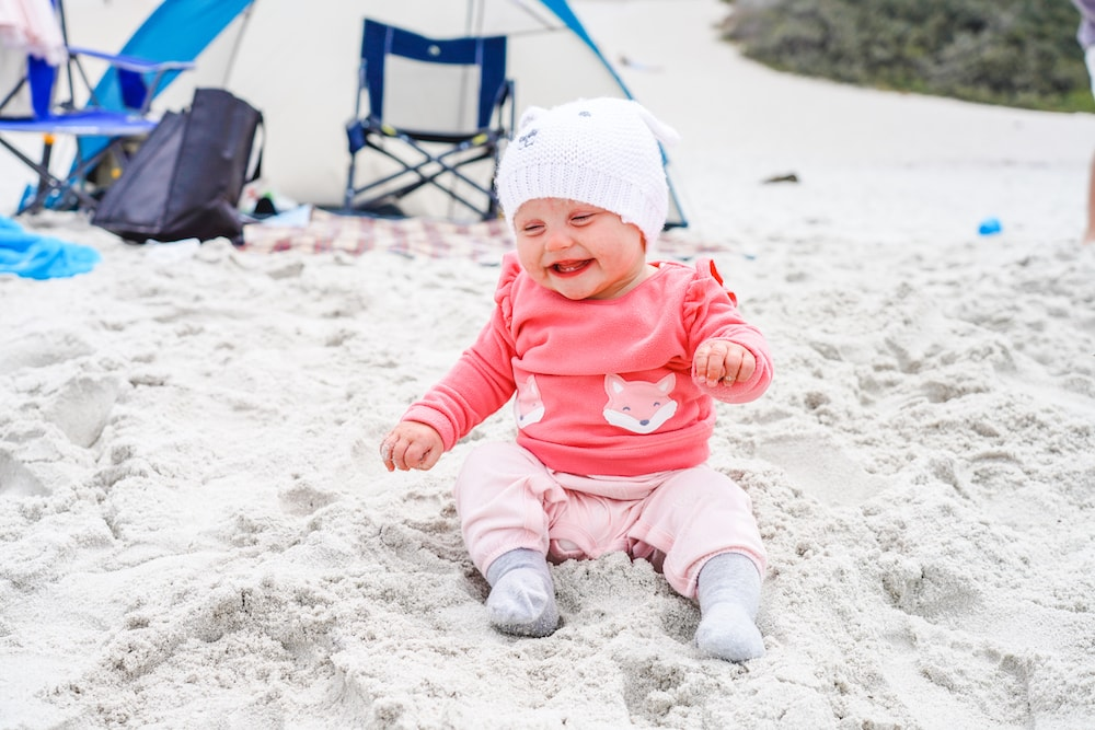 A baby sitting in the sand at Carmel Beach.