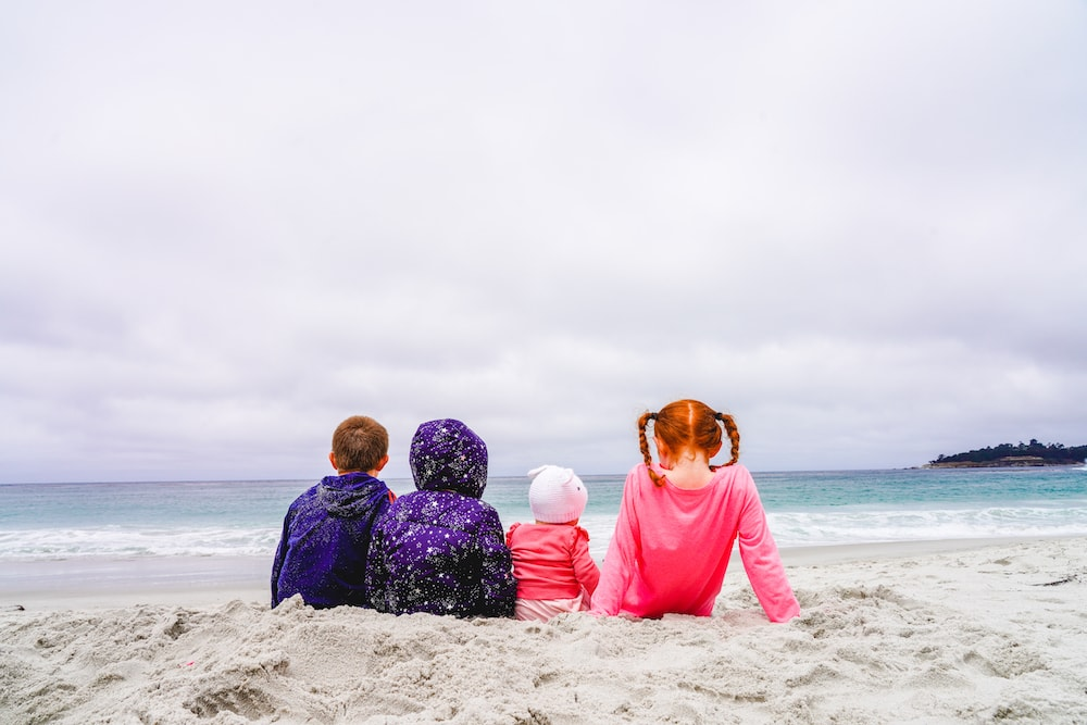 The backs of four kids sitting in the sand at Carmel Beach and looking at the Pacific Ocean.