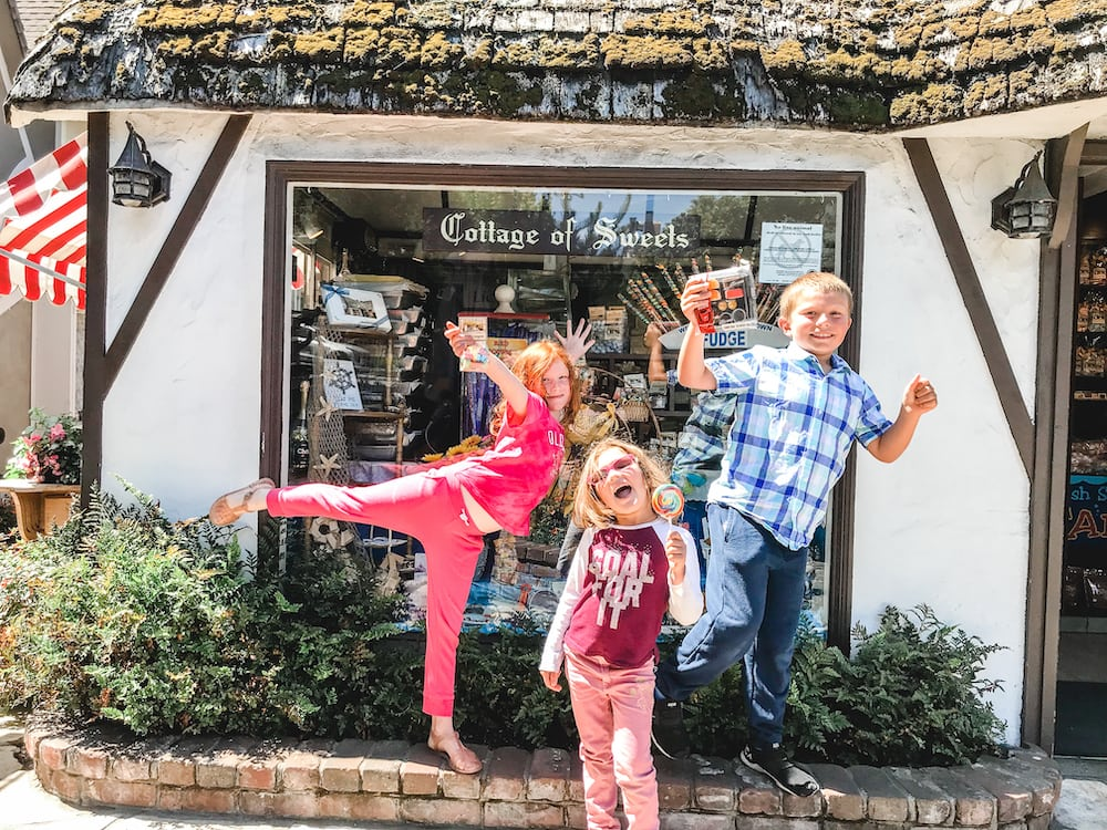 Three kids standing in front of the Cottage of Sweets in Carmel-by-the-Sea.