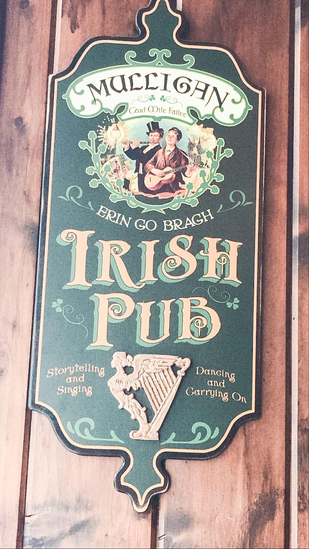 "A wooden sign that says ""Mulligan's Irish Pub""."