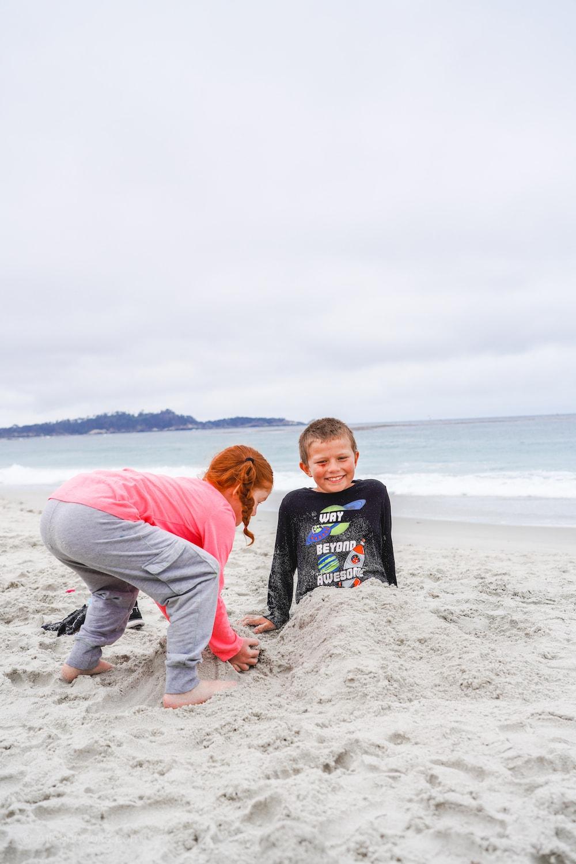 A girl burying a boy. in the sand at Carmel Beach