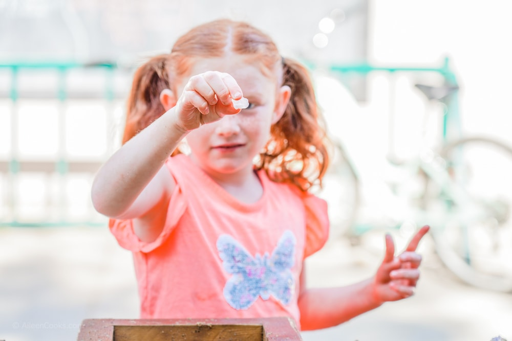 A little girl with red hair, holding up a gem she found during gem mining at Jellystone Park.