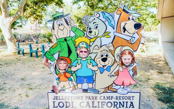 Three kids posing with a Yogi Bear Jellystone Park sign.