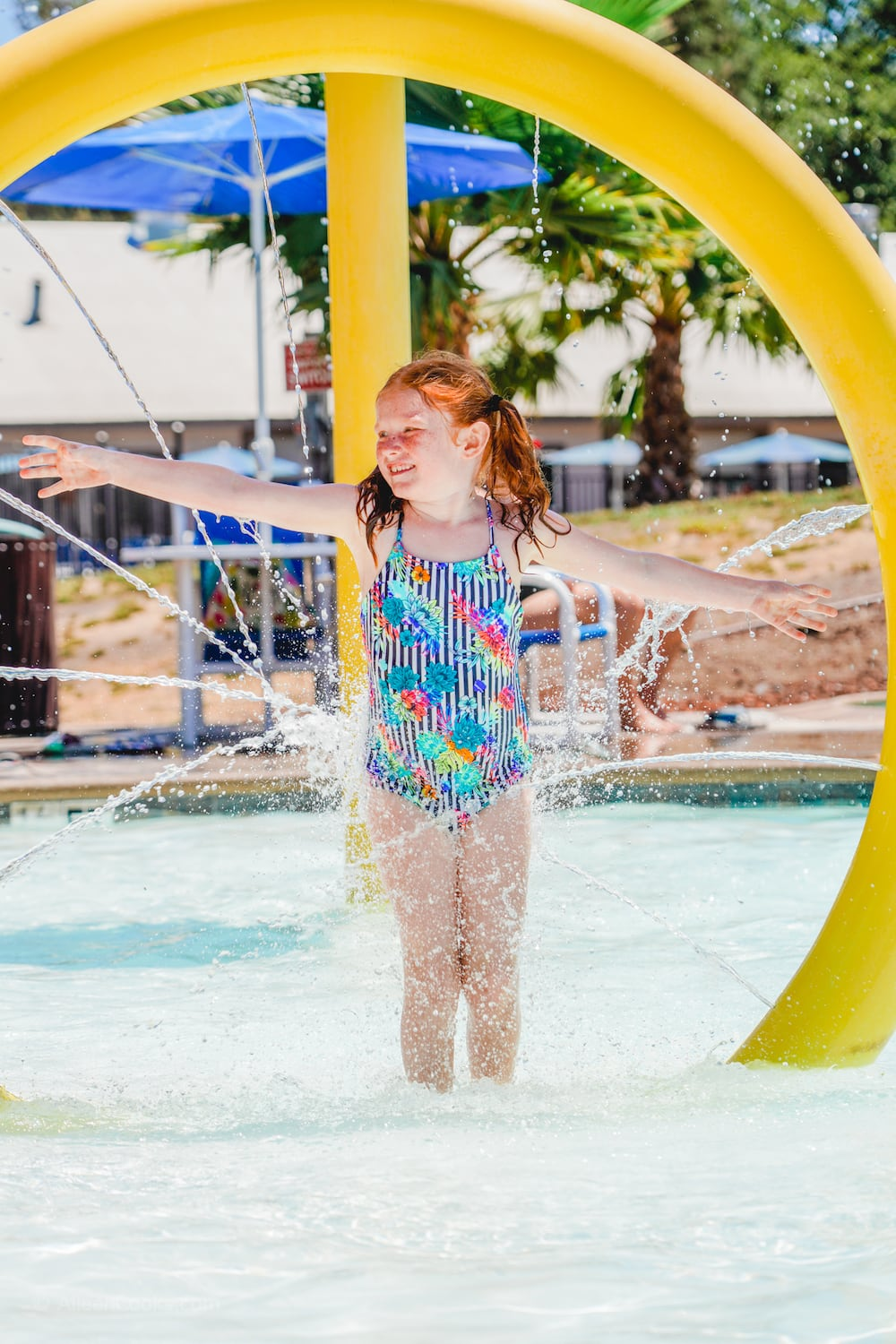 A girl standing inside of a spraying water feature in one of the pools at Tower Park.