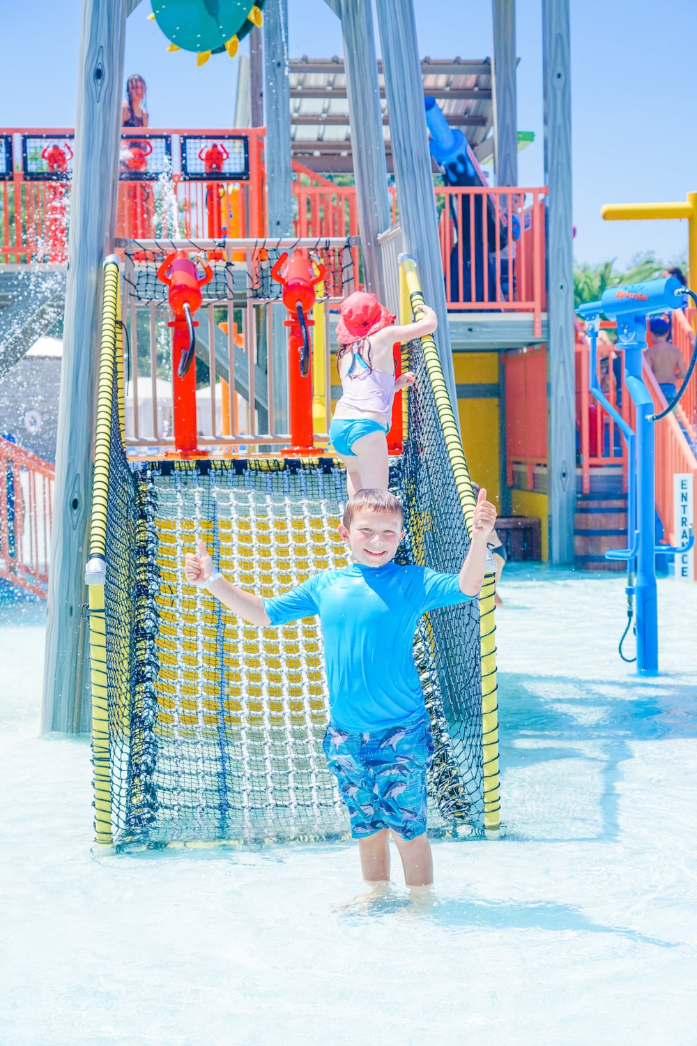 A boy in a blue swim suit standing inside the Jellystone Park water playground.