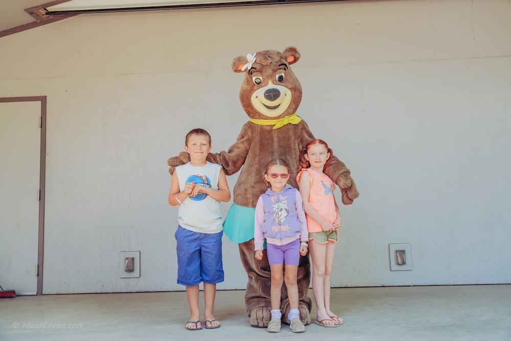Three kids standing with Cindi Bear at Yogi Bear's Jellystone Park.