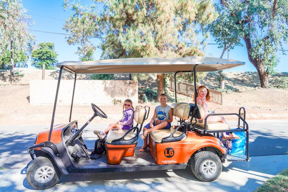 Three kids sitting inside of a large golf cart.
