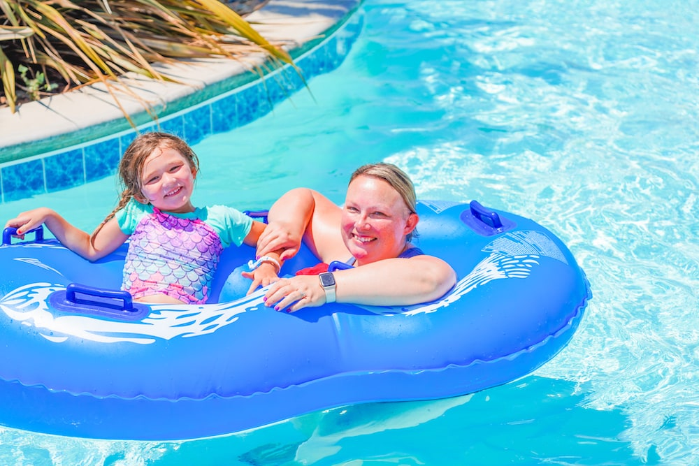 A mother and daughter sitting in a double tube on the lazy river at Tower Park Camp-Resort.