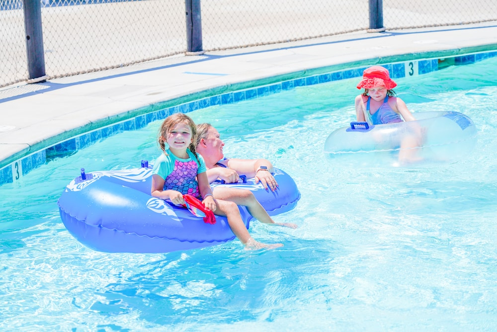 A mom with her two daughters sitting in blue inner tubes on a lazy river.