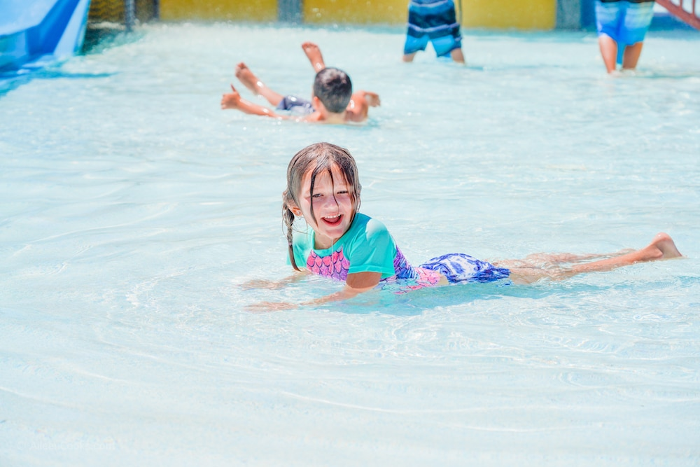 A little girl laying in the shallow water of a water playground and smiling.