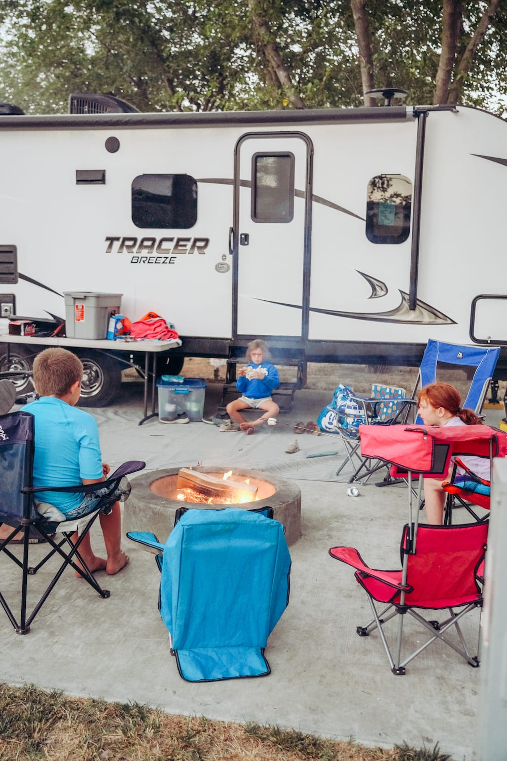 Three kids sitting our a campfire, in front of a travel trailer.