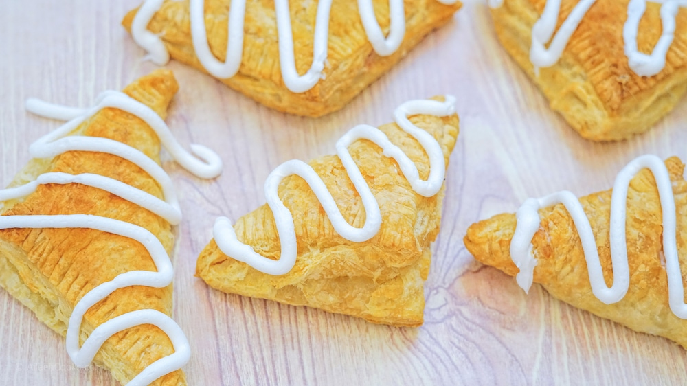 Pumpkin hand pies drizzled with white icing, on top of parchment paper.