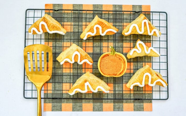 A cooling rack filled with air fried pumpkin turnovers.