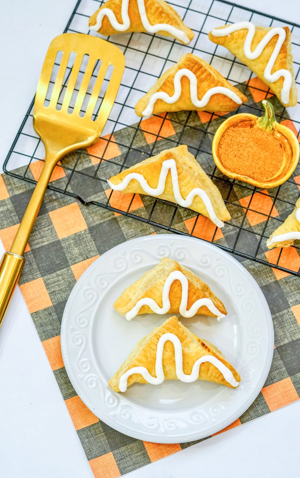 Two pumpkin hand pies on a white plate, next to a cooling rack of pumpkin hand pies.