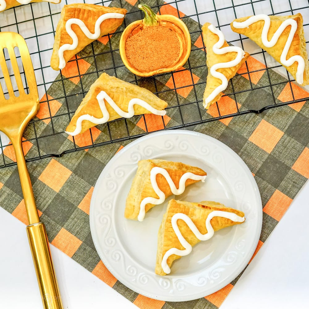 An orange and black checkered placemat topped with a cooling rack of pumpkin hand pies.