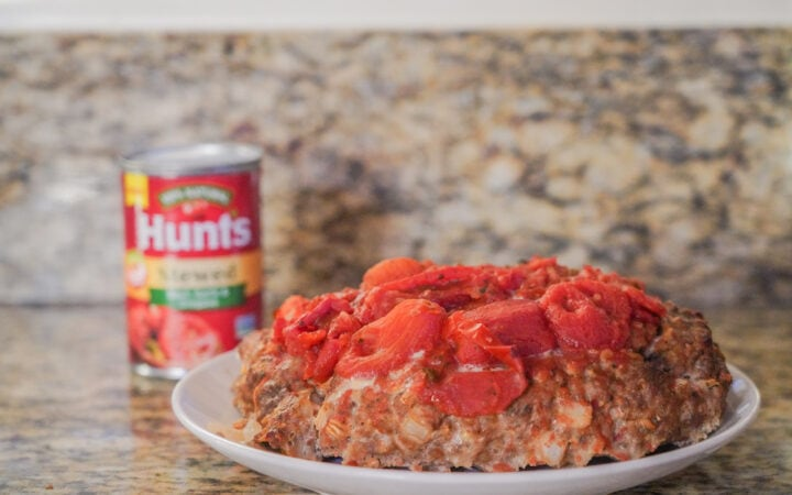 A dish of meatloaf, topped with stewed tomatoes.