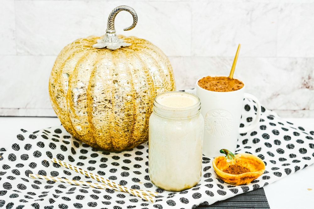 A jar of homemade creamer in front of a white mug of coffee and decorative pumpkin.