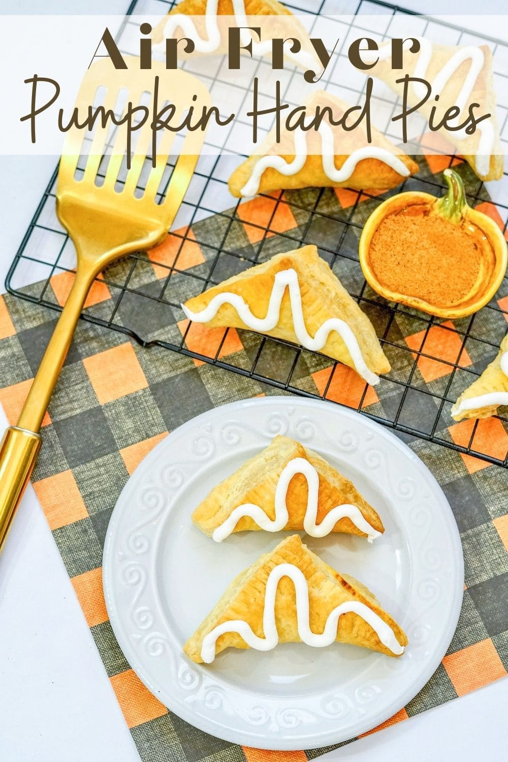 """Two pumpkin hand pies on a white plate with the words """"Air Fryer Pumpkin Hand Pies"""" in brown lettering at the top of the image."""